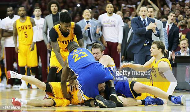 Draymond Green and David Lee of the Golden State Warriors fall on top of Matthew Dellavedova of the Cleveland Cavaliers in the fourth quarter during...