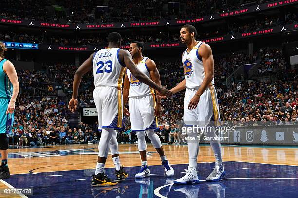Draymond Green and James Michael McAdoo of the Golden State Warriors give each other fives against the Charlotte Hornets at Spectrum Center on...