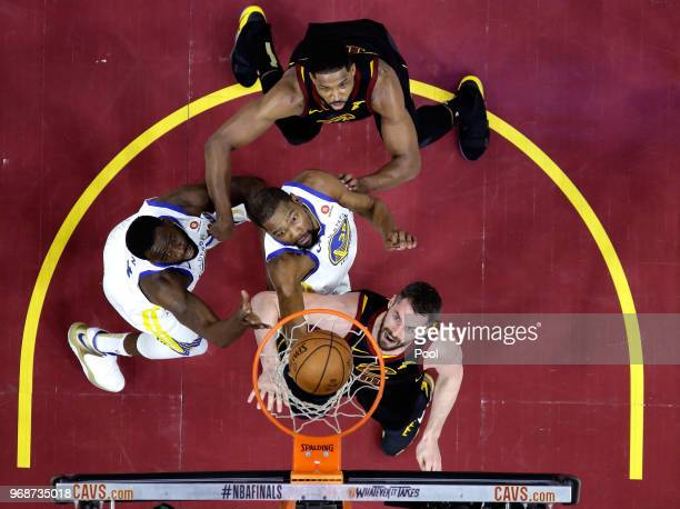 Draymond Green and Kevin Durant of the Golden State Warriors battle for position with Kevin Love and Tristan Thompson of the Cleveland Cavaliers in...