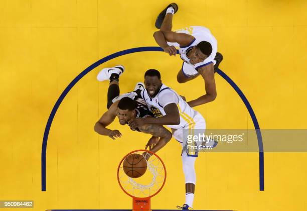 Draymond Green and Kevon Looney of the Golden State Warriors go up for a rebound against Rudy Gay of the San Antonio Spurs during Game Five of Round...