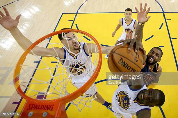 Draymond Green and Klay Thompson of the Golden State Warriors go up for a rebound against Kyrie Irving of the Cleveland Cavaliers in the second half...
