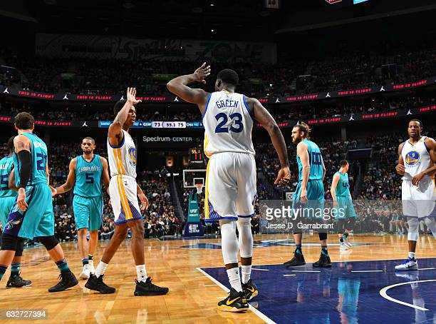 Draymond Green and Patrick McCaw of the Golden State Warriors give each other fives against the Charlotte Hornets at Spectrum Center on January 25...