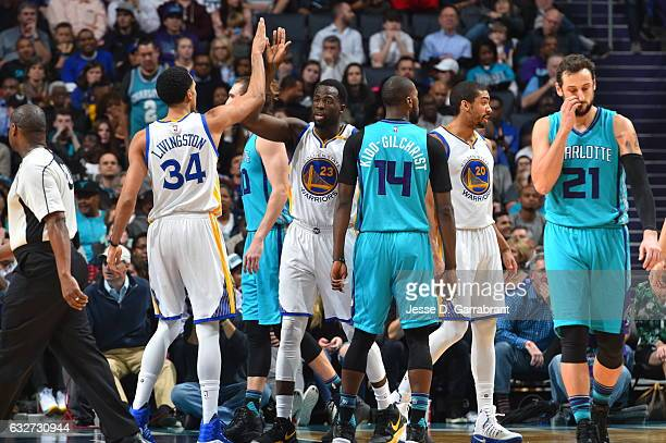 Draymond Green and Shaun Livingston of the Golden State Warriors give each other fives against the Charlotte Hornets at Spectrum Center on January 25...