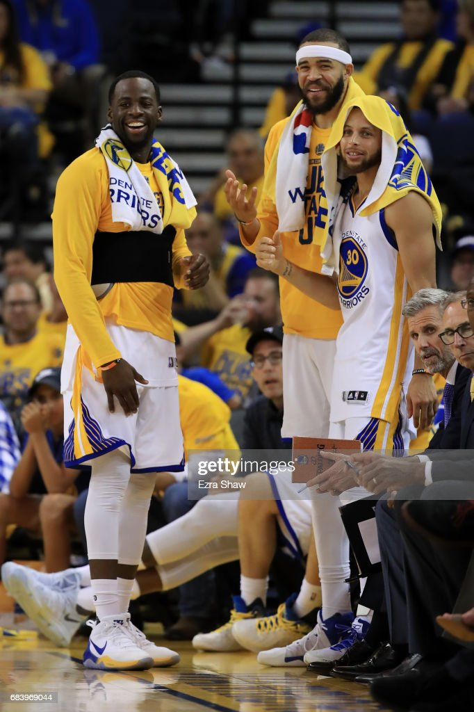 Draymond Green #23, JaVale McGee #1, and Stephen Curry #30 of the Golden State Warriors smile on the bench in the final moments of their 136-100 win over the San Antonio Spurs in Game Two of the NBA Western Conference Finals at ORACLE Arena on May 16, 2017 in Oakland, California.