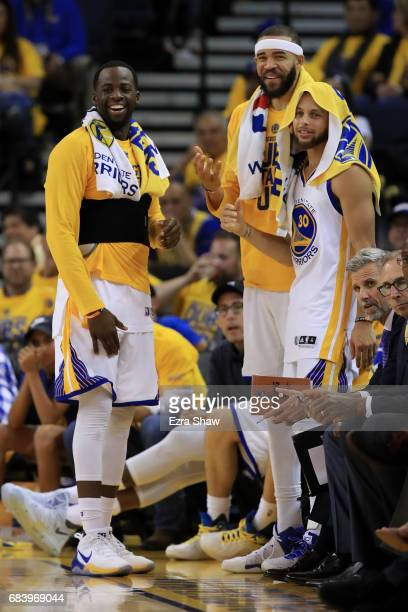 Draymond Green JaVale McGee and Stephen Curry of the Golden State Warriors smile on the bench in the final moments of their 136100 win over the San...