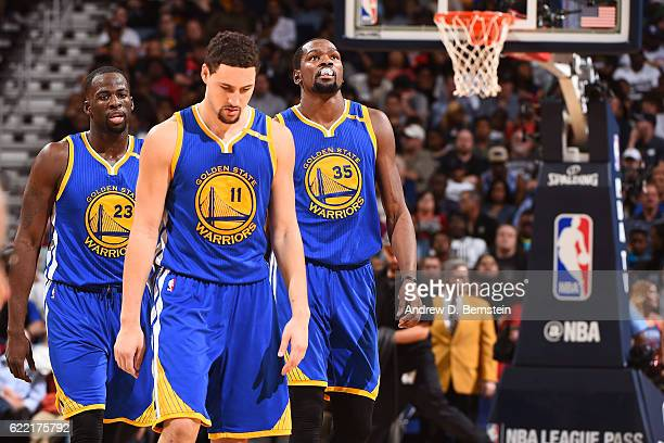Draymond Green Kevin Durant and Klay Thompson of the Golden State Warriors stand on the court during a game against the New Orleans Pelicans at...