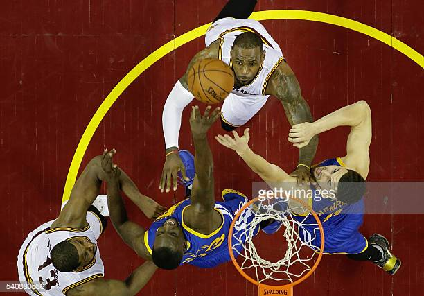 Draymond Green of the Golden State Warriors attempts to rebound the ball as Klay Thompson, LeBron James of the Cleveland Cavaliers, and Tristan...