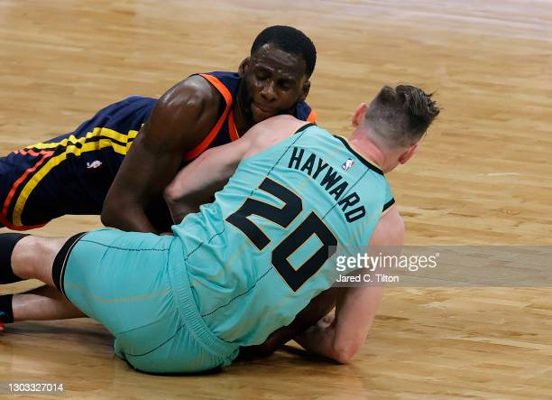 Draymond Green of the Golden State Warriors battles for possession with Gordon Hayward of the Charlotte Hornets during the fourth quarter of their...