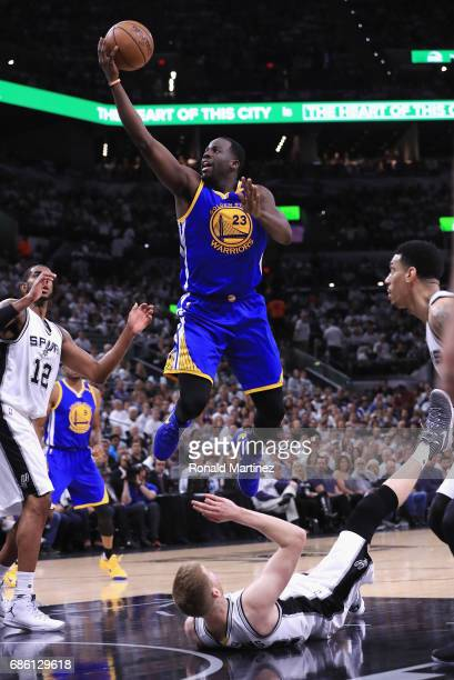 Draymond Green of the Golden State Warriors drives to the basket as Davis Bertans of the San Antonio Spurs falls down in the first half during Game...