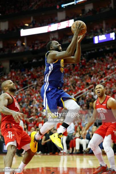 Draymond Green of the Golden State Warriors goes up for a shot defended by Eric Gordon of the Houston Rockets and PJ Tucker of the Houston Rockets in...