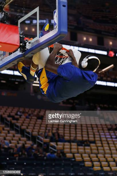 Draymond Green of the Golden State Warriors hangs from the rim during the warm up before the game against the Houston Rockets at Chase Center on...