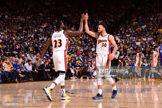 Draymond Green of the Golden State Warriors highfives Stephen Curry of the Golden State Warriors against the LA Clippers on April 7 2019 at ORACLE...