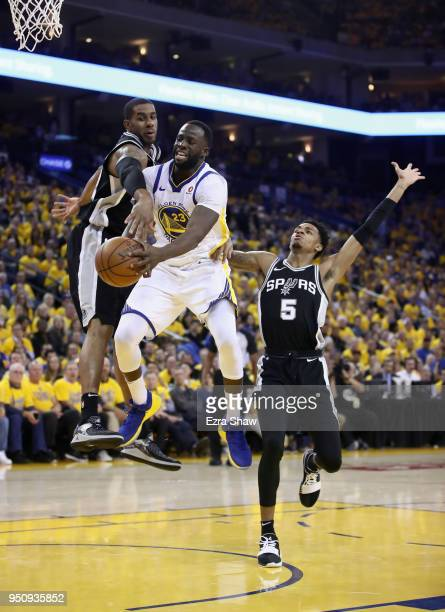 Draymond Green of the Golden State Warriors passes around LaMarcus Aldridge and Dejounte Murray of the San Antonio Spurs during Game Five of Round...