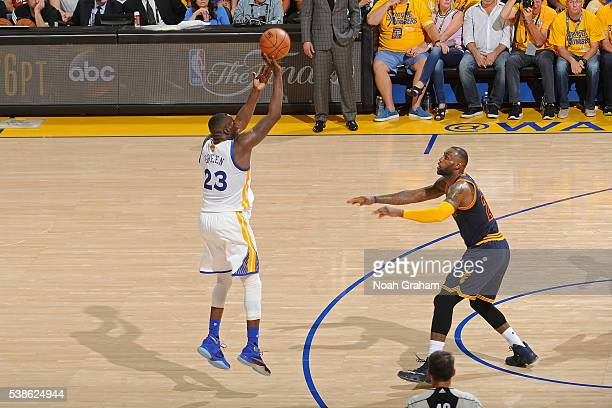 Draymond Green of the Golden State Warriors shoots a three point basket while guarded by LeBron James of the Cleveland Cavaliers during Game Two of...