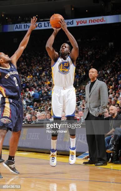 Draymond Green of the Golden State Warriors shoots against Darius Miller of the New Orleans Pelicans on December 17 2013 at Oracle Arena in Oakland...