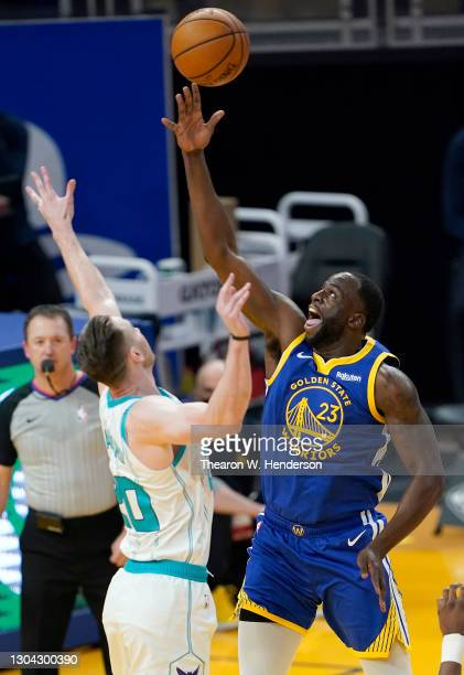 Draymond Green of the Golden State Warriors shoots over Gordon Hayward of the Charlotte Hornets during the first half of an NBA basketball game at...