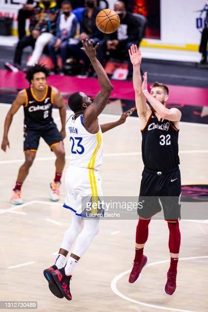 Draymond Green of the Golden State Warriors shoots the ball as Dean Wade of the Cleveland Cavaliers defends during the fourth quarter at Rocket...