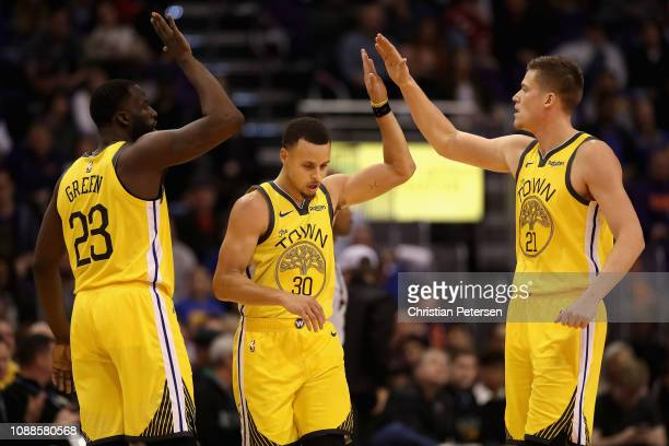 Draymond Green Stephen Curry and Jonas Jerebko of the Golden State Warriors highfive after scoring against the Phoenix Suns during the second half of...