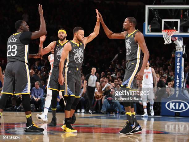 Draymond Green Stephen Curry and Kevin Durant of the Golden State Warriors exchange high fives during the game against the New York Knicks on...