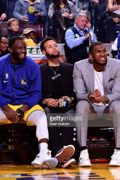 Draymond Green Stephen Curry and Kevon Looney of the Golden State Warriors look on against the Boston Celtics on November 15 2019 at Chase Center in...