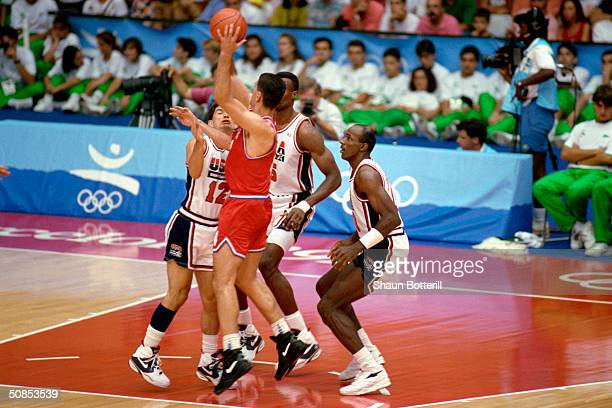 Drazen Petrovic of Croatia is triple teamed by John Stockton David Robinson and Clyde Drexler of the United States in the 1992 Olympic game on August...