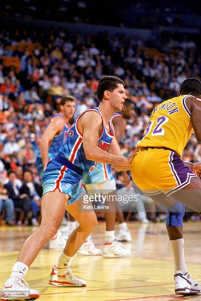 Drazen Petrovic of the New Jersey Nets covers Earvin Magic Johnson of the Los Angeles Lakers during a 199091 season game at the Great Western Forum...