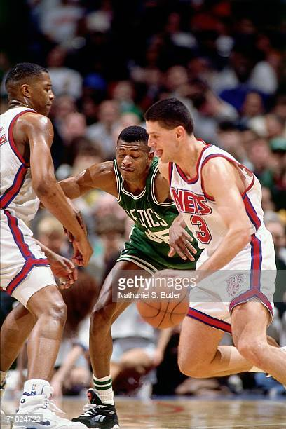 Drazen Petrovic of the New Jersey Nets drives against Reggie Lewis of the Boston Celtics during a game circa 1992 at the Brendan Byrne Arena in East...