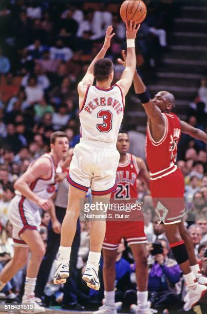 Drazen Petrovic of the New Jersey Nets shoots against Michael Jordan of the Chicago Bulls at the Brendan Byrne Arena in East Rutherford NJ circa 1991...