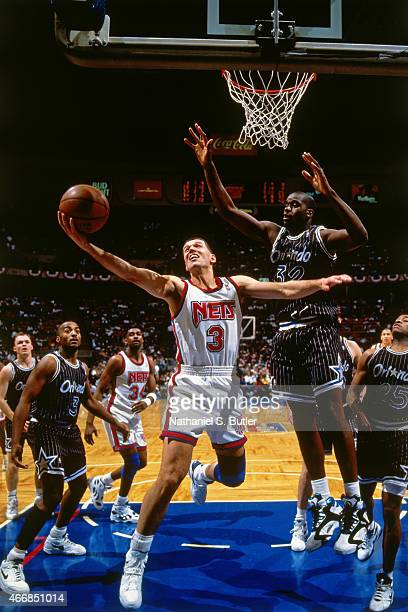 Drazen Petrovic of the New Jersey Nets shoots against Shaquille O'Neal of the Orlando Magic circa 1993 at Brenda Bryne Arena in East Rutherford New...