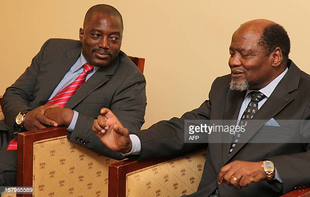 DRCongo President Joseph Kabila confers with the former President of Mozambique Joaquim Chisano as they attend on December 82012 the Extraordinary...