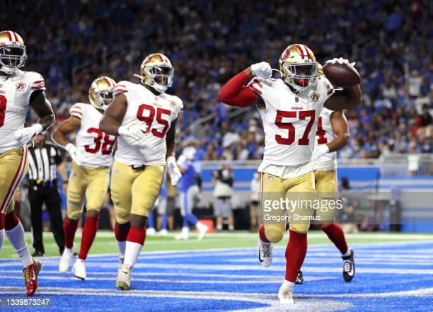 Dre Greenlaw of the San Francisco 49ers celebrates with teammates after a 39-yard interception return from a pass from Jared Goff of the Detroit...