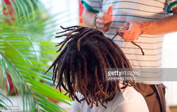 Dreadlock artist Ananda Rieber repairs and maintains a man's dread hairstyle in his flat in Berlin on July 9 2013 USE