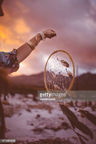 Dream catcher being held up in a natural evening landscape