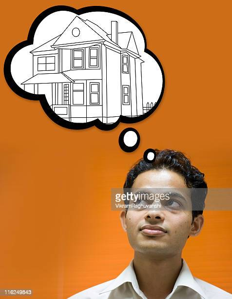 Dream House Indian youth dreaming about his fantasy home vertical