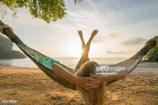 Dream life, female relaxing in hammock on tropical beach