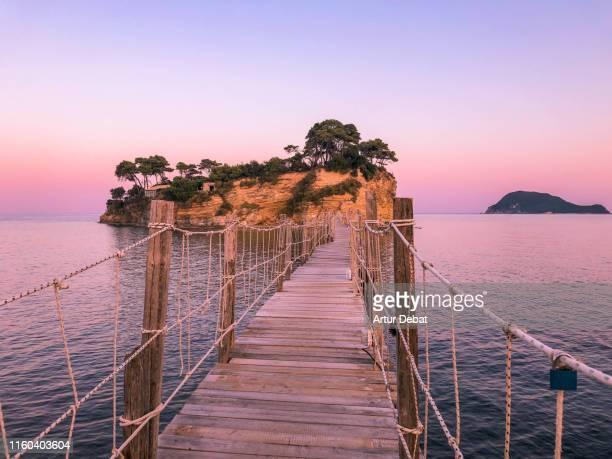 dreamlike small island with wooden bridge in greece during sunset. - loopbrug stockfoto's en -beelden