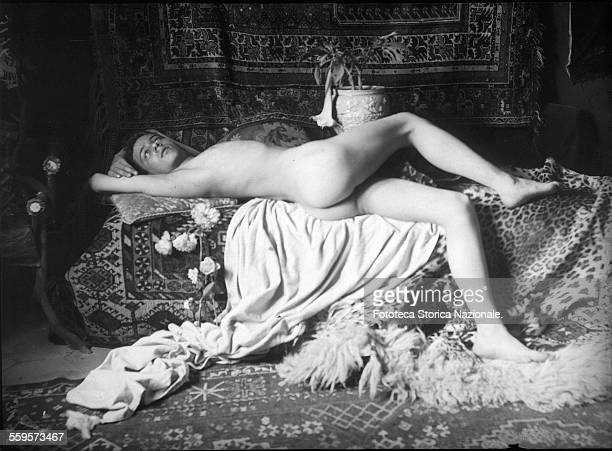 Dreamy Boy Male nude very chaste but sensual lying on cushions and carpets Photography attributed to Wilhelm von Plüschow Italy approx 1900
