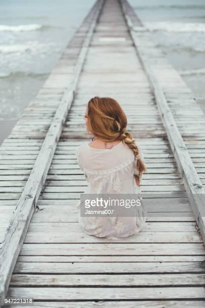 dreamy girl on beach - solitario foto e immagini stock