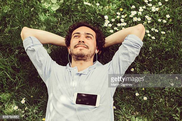 dreamy man in the grass - serene people stock pictures, royalty-free photos & images