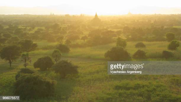 dreamy sunset over green bagan plains, myanmar - argenberg stock-fotos und bilder