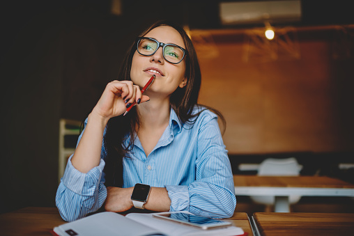 Dreamy woman podring while working on journalistic publication sitting with notebook in cafe,thoughtful female student in eyewear doing homework task solving problems and analyzing information 1161370536