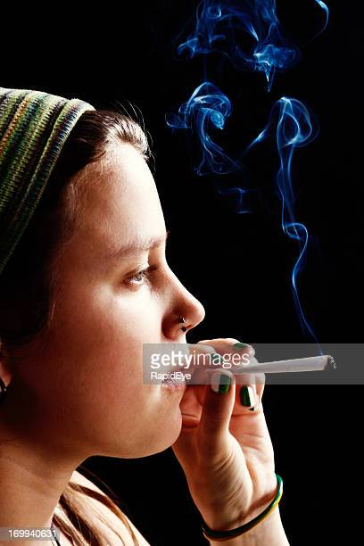 Dreamy young woman about to puff on marijuana cigarette