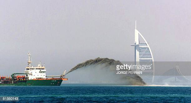 A dredger barge pumps sand onto the sea bed 3 miles off the shore of Dubai as the Palm Island development gets in full gear 05 May 2002 with the Burj...