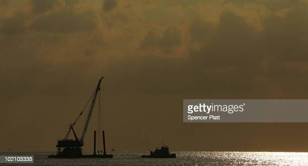 A dredger is pulled out to sea for work on the oil spill June 15 2010 in Grand Isle Louisiana The BP spill has been called the largest environmental...