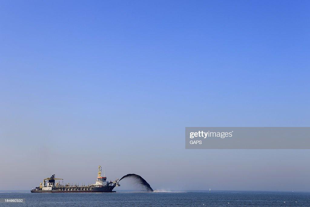 dredger pumping sand onto the coastline : Stock Photo