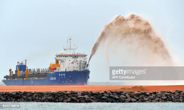 A dredger pumps sand to reclaim land just outside a port in the Sri Lankan capital Colombo on September 6 as part of a USD 14billion real estate...