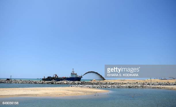 A dredger pumps sand to reclaim land just outside the port of Colombo on March 7 as part of a USD 14billion real estate development by China The...