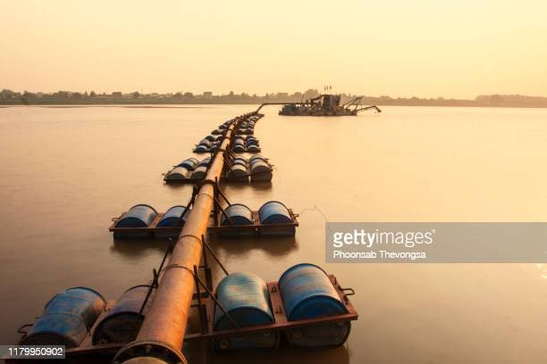 dredging boat carrying a sand pumping machine near mekong riverbank in vientiane, laos - 浚渫 ストックフォトと画像