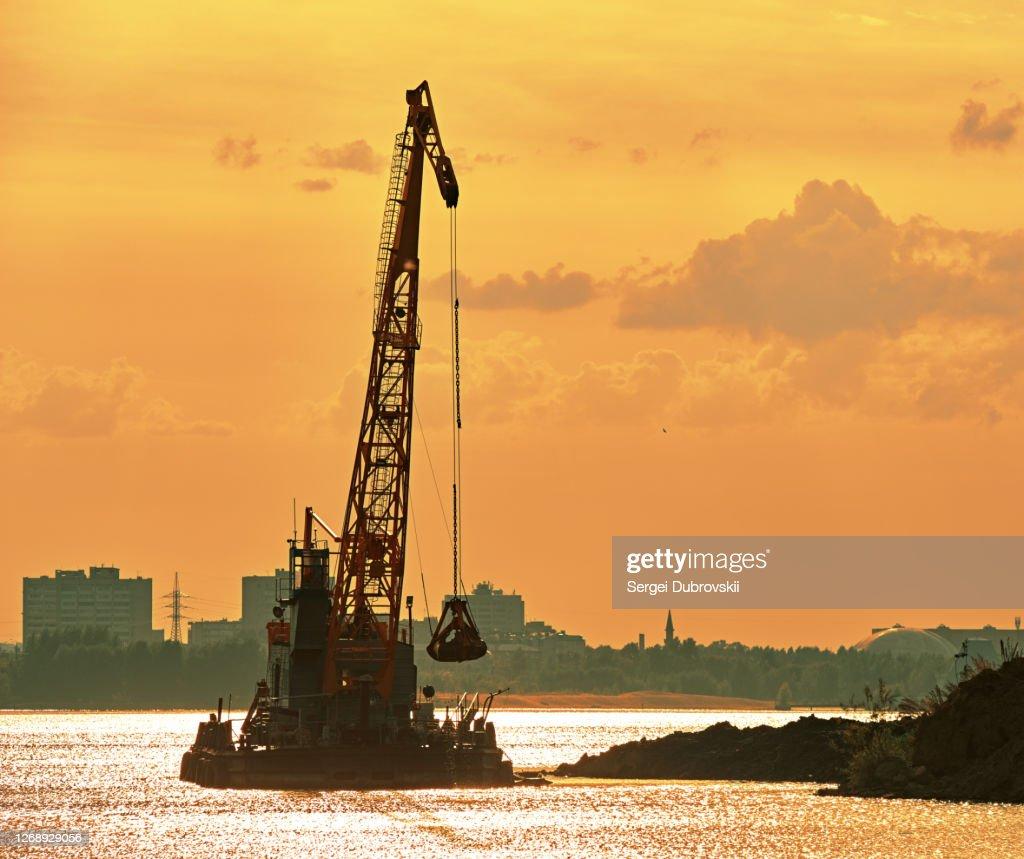 海岸の近くで働く浚渫クレーン、バックイブニングオレンジの日光反射 : ストックフォト