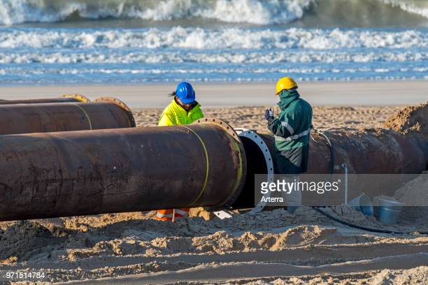 Dredging workers connecting pipes of pipeline during sand replenishment / beach nourishment works along the Belgian coast at Ostend Belgium